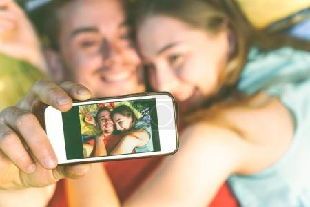 Young couple of lovers taking lying on grass taking a selfie with mobile phone - Happy teenagers in love making a self portrait using smartphone camera - Warm vintage filter -