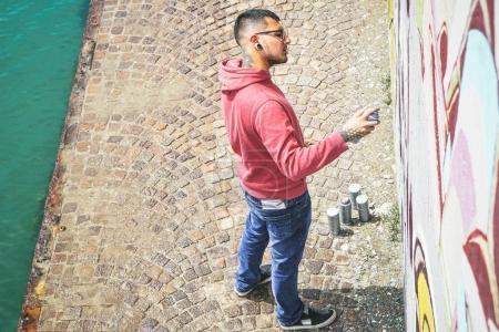 Photo pour Street graffiti artiste peinture avec un spray couleur peut une murale graffiti sur le mur - Urbain, style de vie, concept d'art de rue - image libre de droit