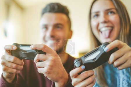 Happy friends playing video games in their apartment - Hilarious young couple having fun with new trend console technology - People entertainment concept - Warm vintage filter - Focus on male hand