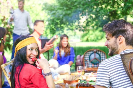 Group of happy friends making a picnic bbq in a park outdoor - Young people having a barbecue party enjoying food and drinks together - Friendship, lifestyle, youth concept - Focus on woman face
