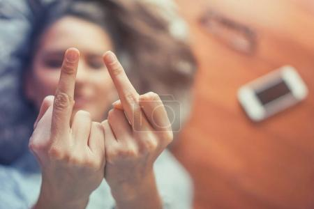 Woman's hand gesturing with middle fingers while lying on the floor of her apartment - Close up of young girl flipping off in front of camera at home - Arrogant, people, youth concept