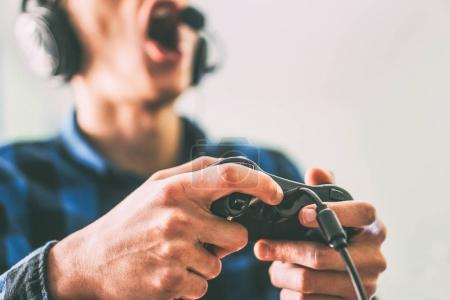Foto de Hombre joven que se divierte jugando juegos de video en línea usando auriculares y micrófono filtro - cerca hombres manos de jugadores con un joystick - Vintage - personas, tecnología, concepto de juegos de azar - Imagen libre de derechos