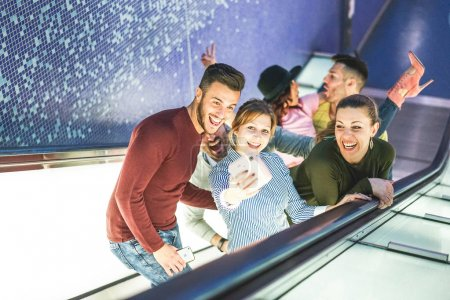 Happy friends taking a photo selfie with instant camera on escalator in metro underground - Group of young people having funny moment taking pictures for social media - Friendship, fun, social concept