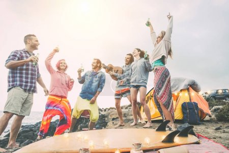 Happy friends dancing and having fun making a beach party in the campsite -  Young people laughing and drinking beers while camping next ocean - Travel, vacation, lifestyle concept