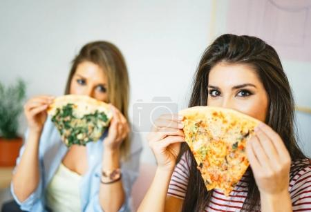 Photo for Young beautiful women eating slices of taste Italian pizza at home - Happy pretty sisters covering their faces with fast food in apartment  - Concept of people, lifestyle, meal - Focus on woman eye - Royalty Free Image