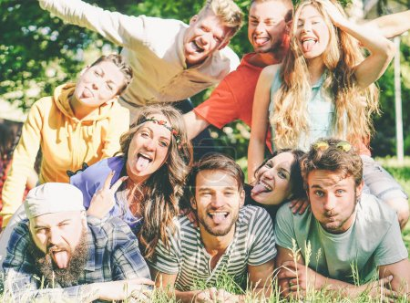 Group of friends having fun together lying on grass while making a self portrait with silly faces - Young happy people taking photo of group at picnic camping park - Friendship and lifestyle concept