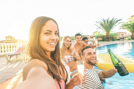 young beautiful women taking a selfie with her friends making pool party drinking champagne - Happy group having fun celebrating with alcohol - Youth,vacation, lifestyle, addiction concept