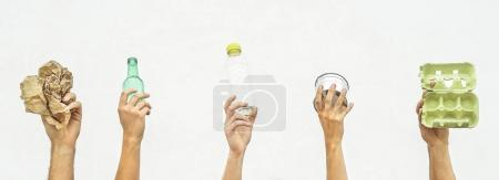 Human hands holding recyclable objects as paper, glass, plastic, aluminium on a white background - Eco concept with recycling - Focus on hands