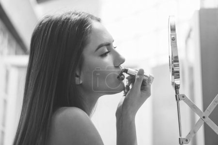Beautiful young woman putting her lipstick on before going out for a night in town - Stunning girl applying makeup on and getting ready to go out in the club - Black and white vintage editing