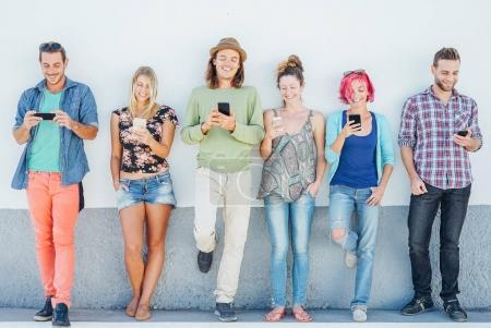 Photo pour Jeunes gens regardent sur leurs téléphones mobiles intelligents, s'appuyant sur un mur - génération accro aux nouvelles technologies - Concept de toxicomanie chez les jeunes aux tendances des réseaux sociaux - image libre de droit
