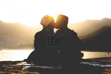 Romantic young couple kissing on the beach on sunset - Silhouette of teens lovers at the beginning of their story sitting on sand - People, love, lifestyle, relationship concept
