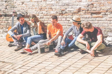 Photo for Group of friends enjoying together a sunny day outdoor listening music with a vintage stereo - Happy young people having fun sitting outside university - Concept of friendship, lifestyle and music - Royalty Free Image