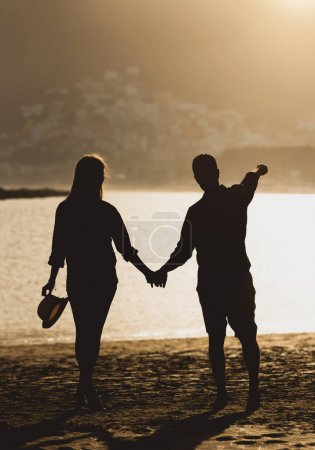Back view of a beautiful young couple of teenagers holding their hands standing on the beach during sunset - Silhoutte of two lovers having a romantic moment on the beach - Love and vacation concept