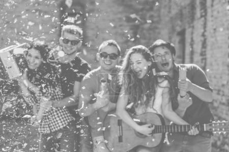 Group of happy friends having fun making a party on street playing guitar and listening music while throwing confetti - Concept of funny people friendship - Black and white edit - Defocused background
