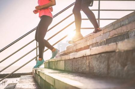 View of runners legs having a workout session on city stairs outdoor - Close up  of people running at sunset - Sport, jogging, health lifestyle  concept -