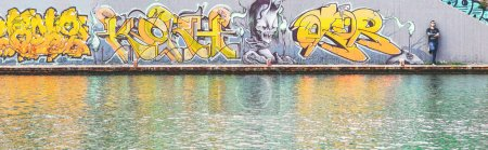 Graffiti writer at the end of his urban paint at river - concept of contemporary artist, lifestyle, street art - Warm filter