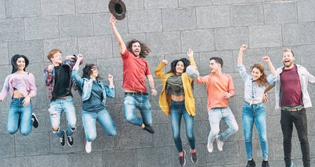 Group of young people jumping together outdoor - Happy millennial friends celebrating success in college - Youth culture lifestyle and friendship concept