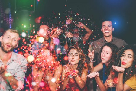 Photo for Happy friends doing party throwing confetti in nightclub - Group young people having fun celebrating new year holidays together in disco club - Youth culture entertainment lifestyle concept - Royalty Free Image