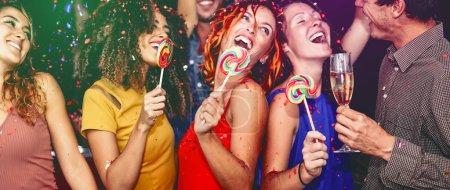 Photo pour Happy friends celebrating new year eve drinking champagne in nightclub - Les jeunes s'amusent à danser avec des sucettes dans un disco club - Youth culture entertainment lifestyle and nightlife concept - image libre de droit