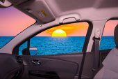 Car window with view of sunset on mediterranean sea, Italy