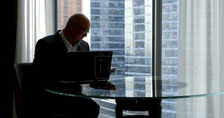 Photo pour Un homme d'âge moyen qui réussit regarde des documents assis à un bureau en verre et un ordinateur portable dans son bureau - image libre de droit