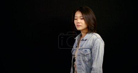 Photo pour Jolie chinoise vêtue d'une veste en denim sourit, debout sur fond noir, portrait moyen - image libre de droit