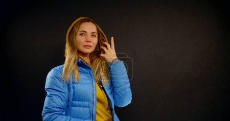 Photo pour Portrait en gros plan d'une belle blonde, elle est au Studio sur un fond noir. Elle pose, Vêtue d'une veste bleue et d'un hoodie jaune sous-jacent, qu'elle ouvre la fermeture éclair.. - image libre de droit