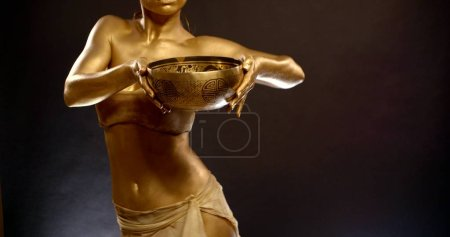 Photo pour Portrait en gros plan d'une fille tonique en haut, elle est au Studio sur un fond noir, elle a un pigment d'or sur sa peau. Mère faisant une danse orientale du ventre. Elle tient une profonde coupe dorée dans sa main. - image libre de droit