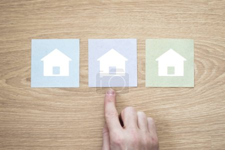 Foto de El hombre de negocios elige un folleto con un icono de casa en casa - Imagen libre de derechos