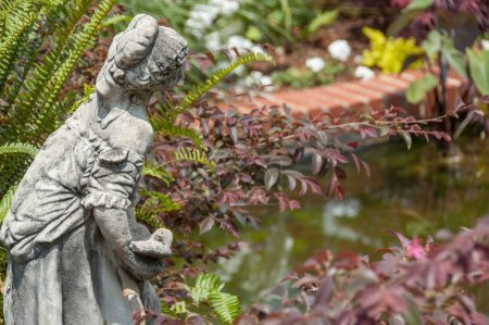Stone statue of a woman overlooking a water feature in a garden