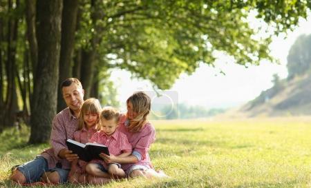 Photo pour Une jeune famille, lecture de la bible dans la nature - image libre de droit
