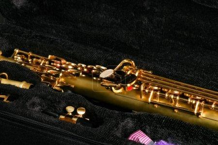 Photo pour Saxophone soprano dans un étui sur fond noir - image libre de droit