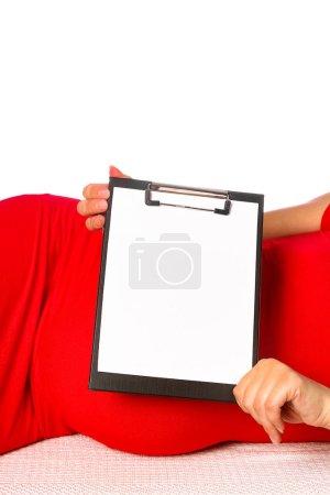 Photo pour La fille enceinte heureuse se trouve sur le fond blanc - image libre de droit