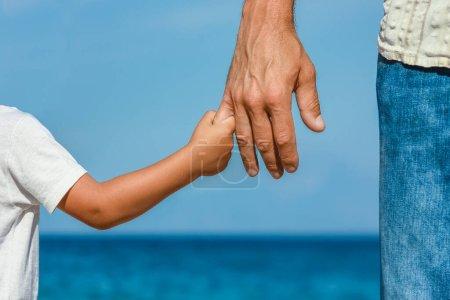 Photo pour Papa heureux retient la main d'un enfant par la mer grecque dans la nature - image libre de droit