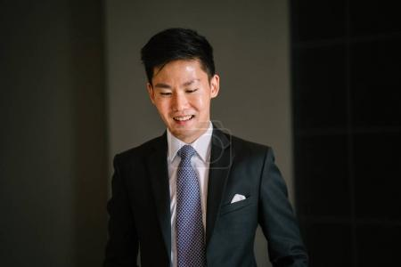 Portrait of a Chinese Asian professional lawyer against a dark background. He is wearing a dark suit, white shirt, blue tie and pocket square. He is relaxed and confident.
