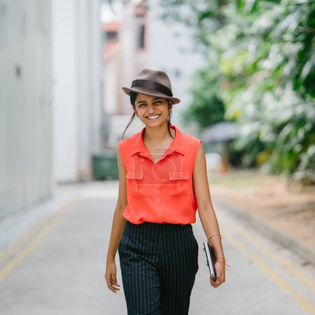young Indian Asian fashionista walks down the street in Asia. She is well-dressed and smiling as she strides down the alley.
