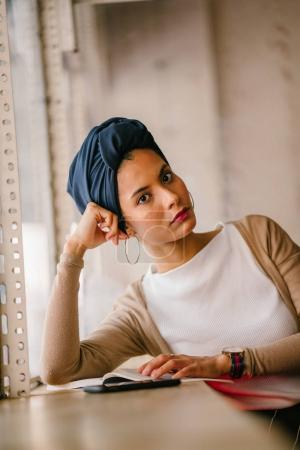 young, attractive Muslim woman (Arab, Malay, Asian) reads a book by the window of a cafe in the day. She is wearing a turban (headscarf, hijabi) and is elegantly dressed in earthy tones.