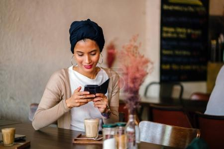 young, attractive Muslim woman (Arab, Malay, Asian)with phone in  cafe in the day. She is wearing a turban (headscarf, hijabi) and is elegantly dressed in earthy tones.
