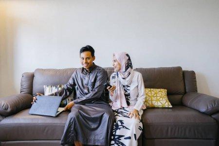 Photo pour Portrait d'un couple musulman malais à la maison avec ordinateur portable lors du festival musulman de Hari Raya à Singapour, en Asie . - image libre de droit