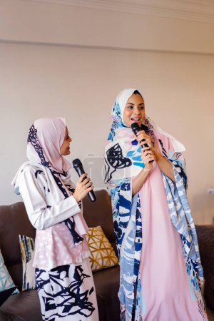 Deux femmes musulmanes en foulard chantent en karaoké sur leur système de divertissement maison sur Hari Raya et apprécient la compagnie des autres