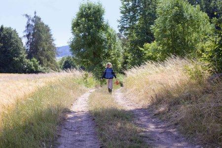 Photo pour Garçon avec un panier Marcher sur une route à la campagne . - image libre de droit