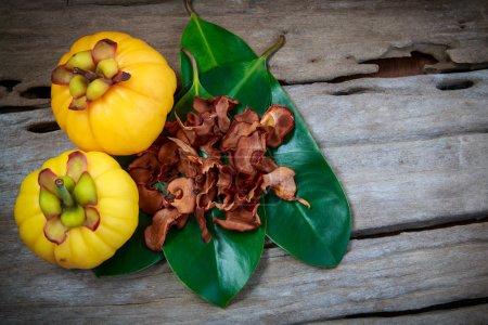Photo pour Vue de dessus. Garcinia cambogia fruits frais sur fond de bois. Garcinia sec sur la feuille. Garcinia atroviridis est une plante d'épices et de la vitamine C élevée et des acides hydroxy citriques (HCA) pour l'alimentation et une bonne santé . - image libre de droit