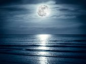 Colorful sky with dark cloud and bright full moon over seascape. Serenity nature background.