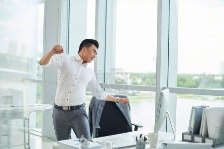 businessman stretching back after hard work