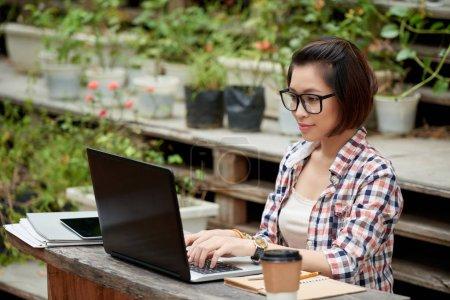 Photo pour Asiatique jeune rédacteur travaillant sur ordinateur en plein air - image libre de droit