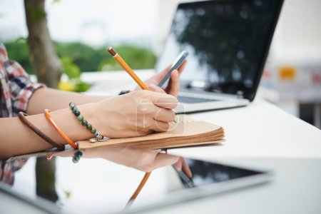 woman taking notes in notepad