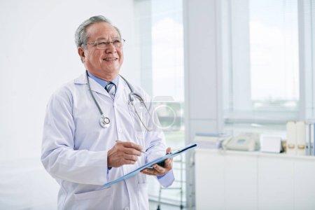 Photo pour Joyeux médecin vietnamien titulaire d'antécédents médicaux - image libre de droit