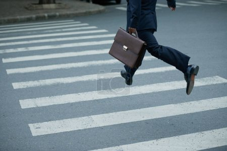 Businessman with briefcase hurry to cross road