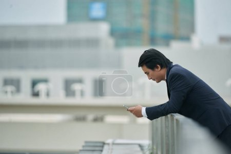 Entrepreneur standing on rooftop and reading message