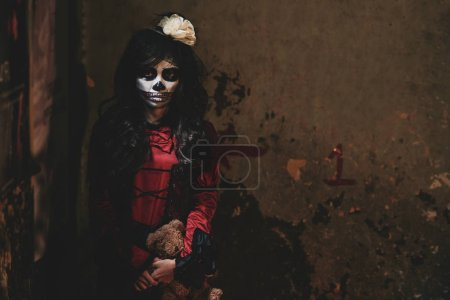Photo for Portrait of bizarre girl with scull face standing in dark corner - Royalty Free Image